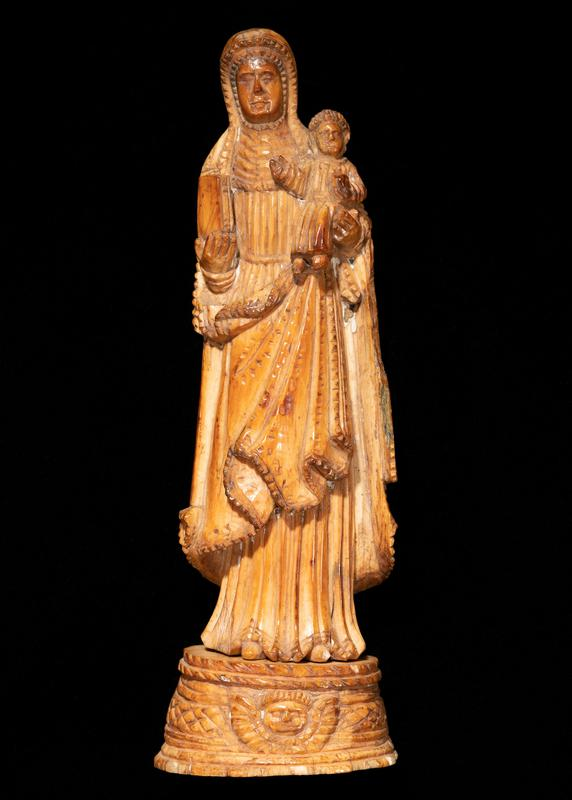 golden brown patina; standing figure of Mary holding a book in her PR hand and a tiny infant Jesus sitting upright held with her PL hand; garments on both figures have many vertical pleats; edging on Mary's headscarf and garments are sawtooth; removable base with winged face at front