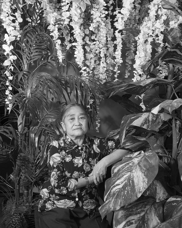 black and white portrait of an elderly woman wearing a blouse with a large floral pattern seated among plastic flowers and foliage; received framed/unglazed
