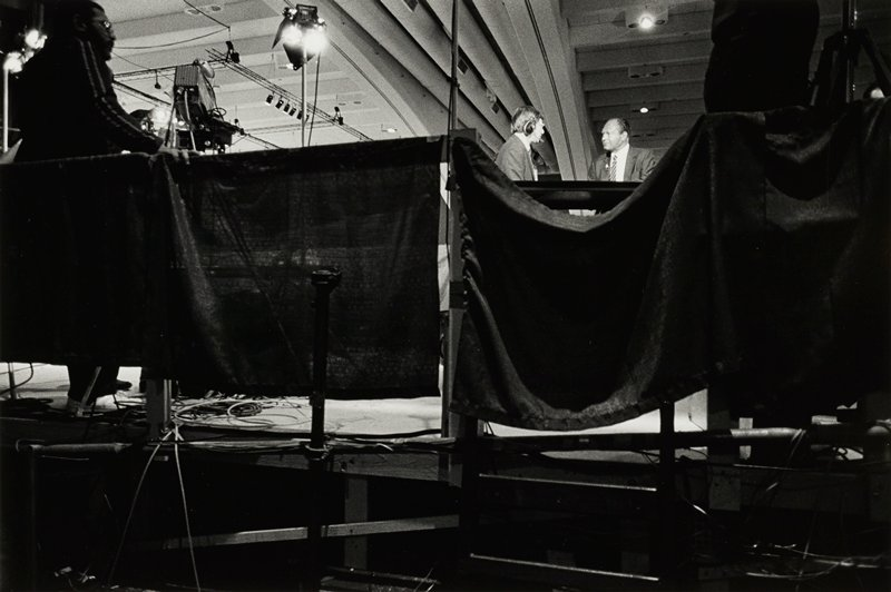 Tom Bradley, right, being interviewed by reporter, left, behind cloth drapes around stage