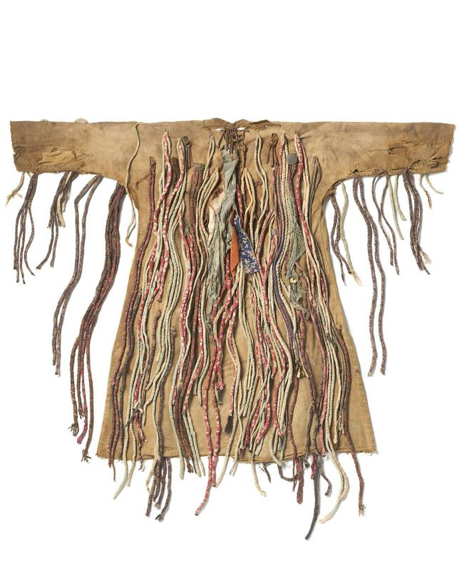 tan cloth coat, with cords of decorative fabric that hang in clumps from top of coat; pieces of metal dangle throughout