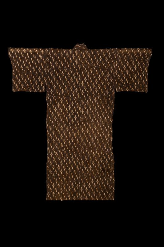 brown robe with tan pattern; repeating pattern consists of two small triangles and two small line and dot symbols; strip of white fabric lining along interior center seam