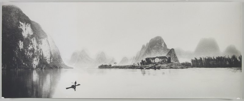 figure wearing a hat, standing on a small boat, holding a paddle, at LLC; buildings in front of light-colored land forms on opposite bank; calm water; Li River, Peoples Republic of China
