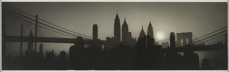 New York skyline in silhouette with sun at R; suspension bridges