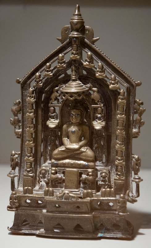 Jain. Central seated figure with inlaid eyes and 3 inlaid jewels on chest; canopy overhanging figure; 23 small figures surrounding largest figure; all seated except 2 standing figures on either side of seated figure; pointed archlike structure