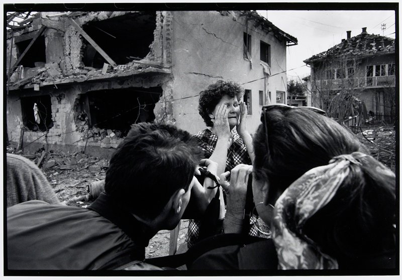 two people photographing distressed woman and bombed-out building