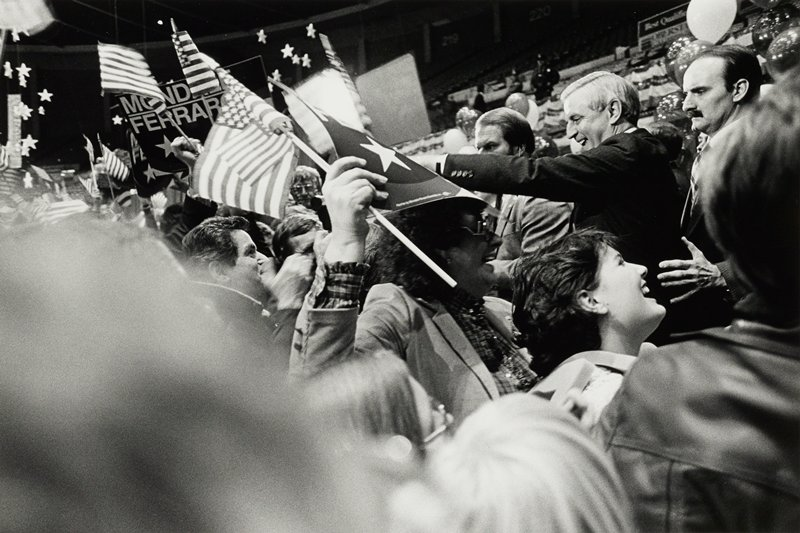 Walter Mondale shaking hands in a crowd at a Mondale/Ferraro political rally; Mondale waving to the crowd flanked by body guards, crowd waving U.S. flags