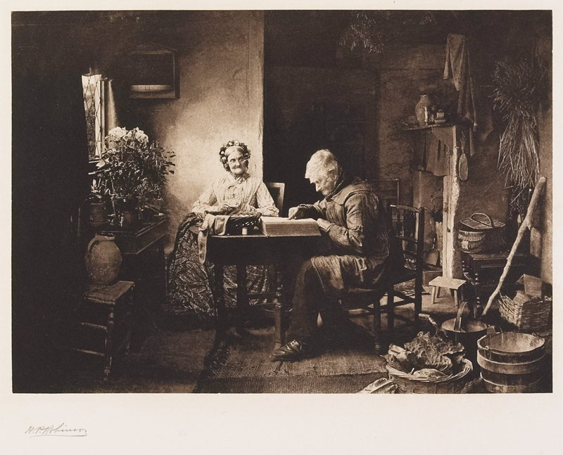 elderly couple seated in interior; woman sewing behind table; man seated at R at table looking at a large book