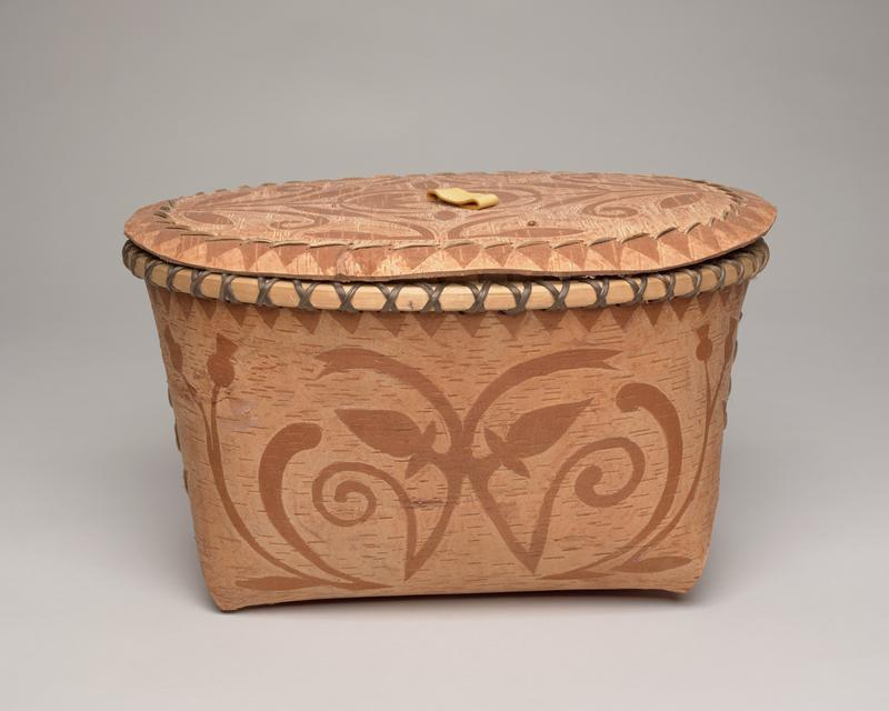 birchbark folded basket with lid; rectangular base, oval opening, oval lid; light brown with darker brown designs: matching floral pattern on front and back, diamond with rays on either side; panels secured on either side with straight stitches; tan interior with three patches of raw bark; overlapping stitches over rim; flat lid with tan leather pull looped through center, tied to stretcher bar on underside; lid top decorated with tulip floral design with triangular pattern around edge and stitches attaching bottom lip worked into triangular pattern; underside of lid raw, white and gray bark