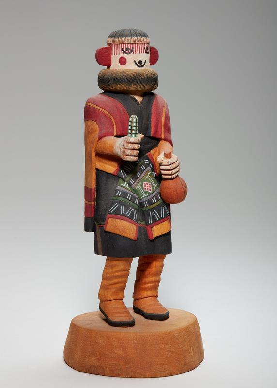 carved, painted figure with an object in each hand (green pattern catcus-like tube in PR hand, container with bulbus end in PL); face with black painted circles and U-shapes for eyes and mouth, red circles on cheeks, and red ears sticking out on either side; vertical red stripes over top half of face; fitted black cap with white edges; brown and black neck piece; tan, red, and black cape over black tunic with green and red stripe around bottom; sash at waist with black, red, green and tan patterns; tan boots with black soles; figure standing on wood round