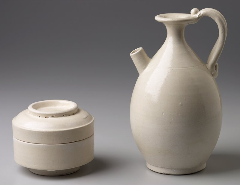 ovoid ewer with thin, tapered neck and flaring mouth; double stranded handle with bead decoration at mouth and shoulder; cylindrical spout at shoulder; flat base; white slip and clear glaze