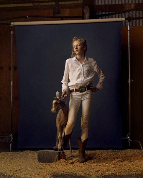image of young, blonde girl in white, button-up shirt and beige pants with leather belt, large belt buckle, and cowboy boots, holding the chain collar around the neck of a brown and white goat; the girl and goat are standing on ground covered with sawdust, in front of a black backdrop with visible frame