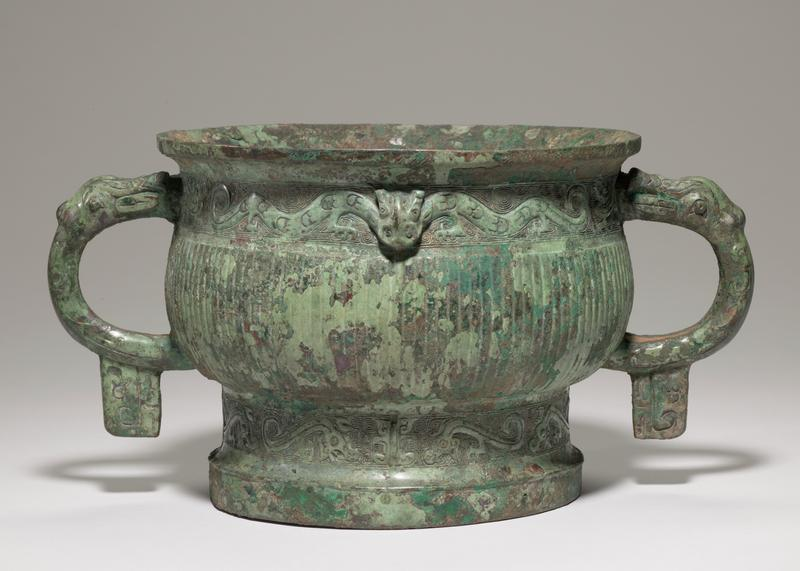 squat vessel with tall foot; rounded body with outward-flaring rim; pair of handles with animal heads and tab-like bottom extensions; vertical incised ribs on body; top band has a pair of dragons each with two serpentine bodies; bottom band has stylized animals; green patina