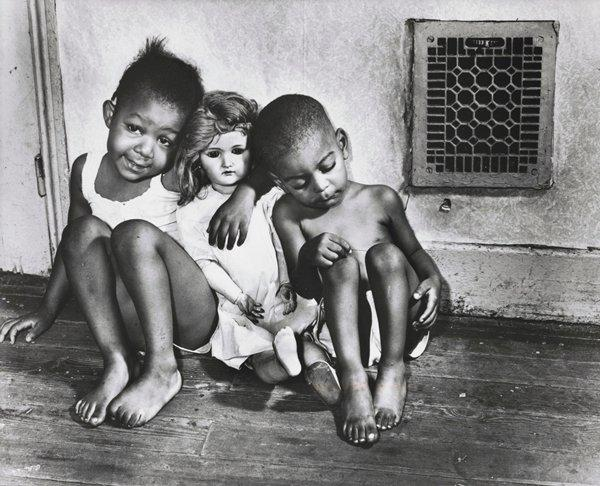 black and white image of two little Black children cuddling with a doll between them, seated on the floor with a decorative heat register grill in wall in URQ; received in black frame