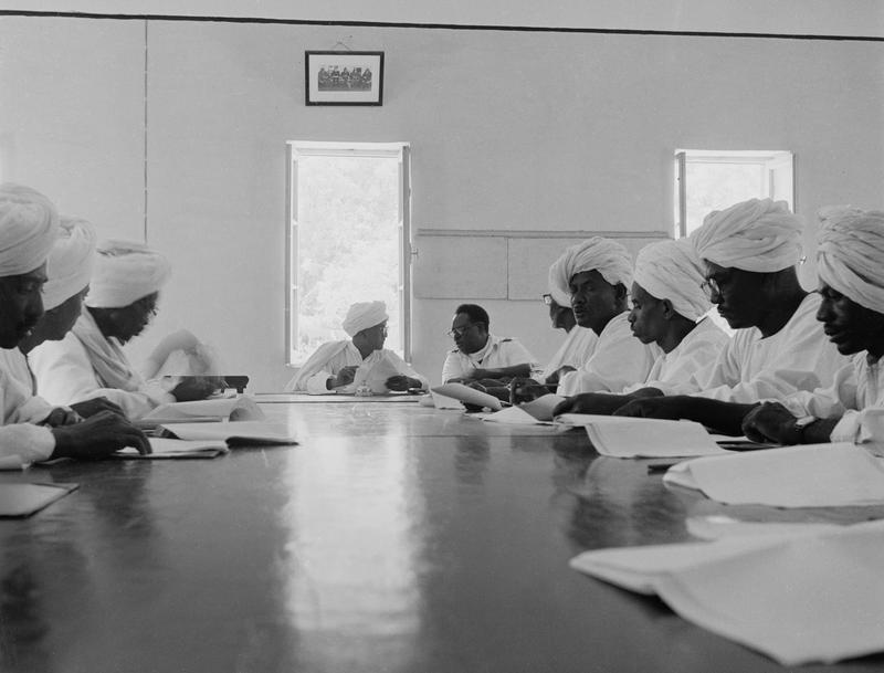 Black and white photograph of ten men wearing white with white wraps on their heads seated around a table with papers in front of them