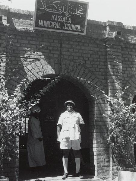 """Black and white photograph of a man wearing white standing in an arch under a sign that says """"Kassala Municipal Council"""""""