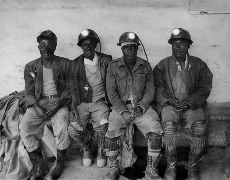 Black and white photograph of four men seated on a bench wearing mining helmets and knee pads