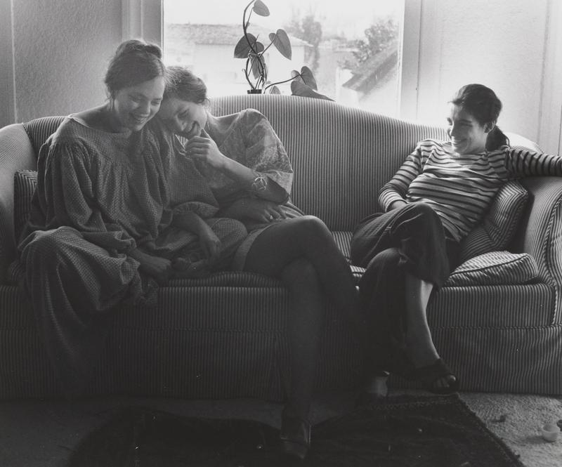 black and white image of three young women seated on a striped couch with a plant in front of a window in background; woman at center has her PL hand beneath her ching and rests her head on shoulder of woman at left