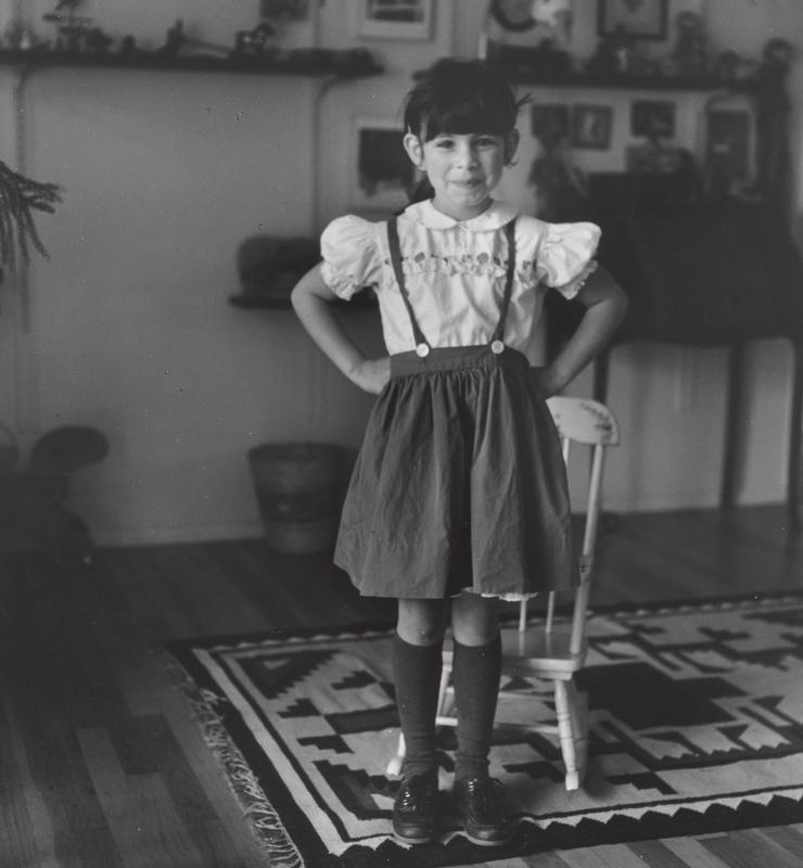 black and white image of a standing girl wearing a pinafore with a white blouse, dark knee high socks and dark shoes, with her hands on her hips