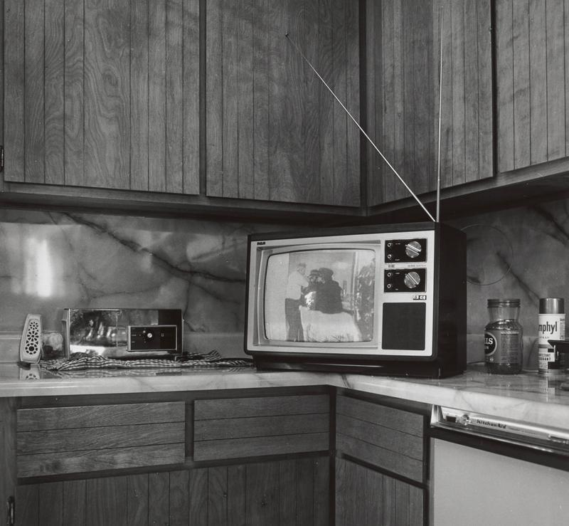 black and white image of a kitchen counter with a TV