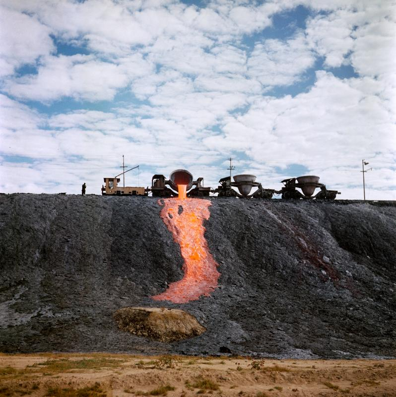 Color image of molten material being dumped down a hillside from a train