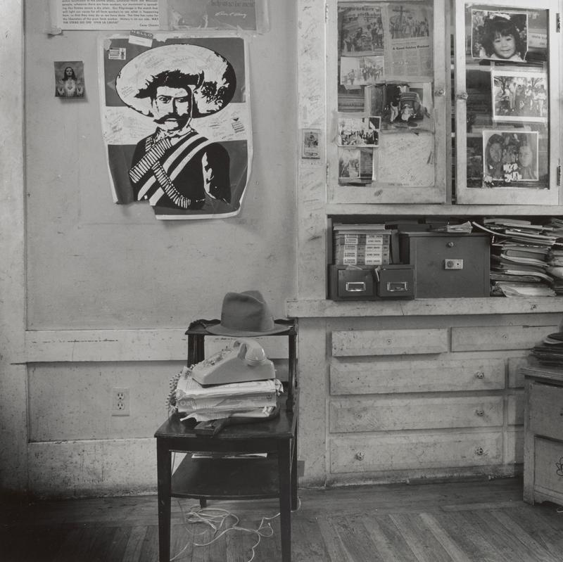 black and white image of a shabby room with a Pancho Villa poster on wall in ULQ; stand with a telephone and hat at center; built-in cabinet at right with file boxes, stacks of papers and photographs on glass doors; same image as .49