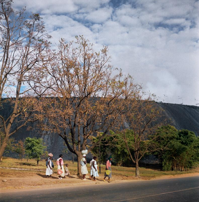 Color photograph of figures, some of which are carrying parcels on their heads, walking beside a road