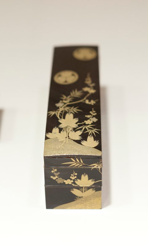 Long, narrow toilet box of black lacquer with gold tree and floral decoration bearing the crest of the Tokugawa family, three asarum (ginger) leaves their points to-gether within a circle; crest appears six tme son box, two on top and two on each side. Box made up of three parts.