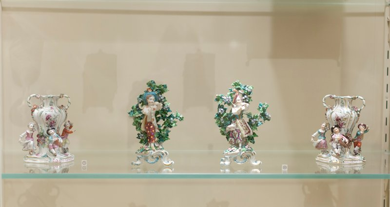 pair of old Chelsea vases comprising three figures of children in dancing attitudes and playing musical instruments around a vase ornamented, delicately painted and encrusted with colored flowers