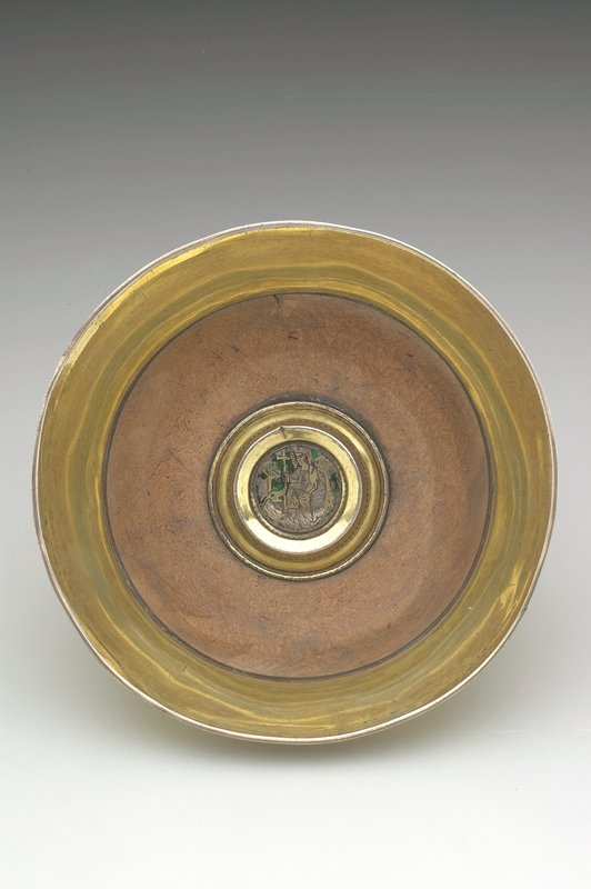 wide maple bowl with wide splayed silver gilt lip; in center is a raised boss enclosing an engraved silver medallion of St. Margaret standing on a dragon