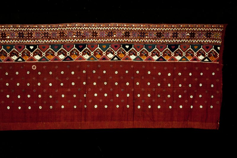 Long strip of dark red cotton with broad embroidered border of geometric designs above which are embroidered cicles. Design suggests that it was used for a skirt.