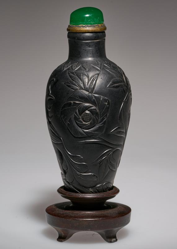 Snuff bottle. The Chinese call this black amber. Others say that it is coal laqured. Green glass top. Carved with the Peony Tree and the Phoenix.
