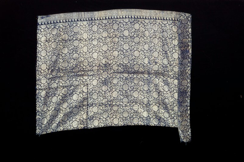 Panel of kincob cloth with pattern of chrysanthemums in gold on deep blue silk ground. Border stripe on one side.