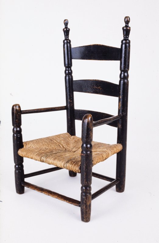 chair, child's with reed seat; three slat back; front of arms considerably worn from having been pushed on floor