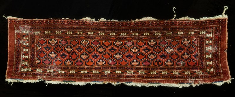Camel bag, Afghan. Bright red field covered with all-over pattern of small hexagons. Three narrow borders all around the field, and an extra one at the top. Sides finished with a selvedge. Ends finished with a web turned under. The fringe which was originally sewed to the bottom end has worn away. Senna knot.