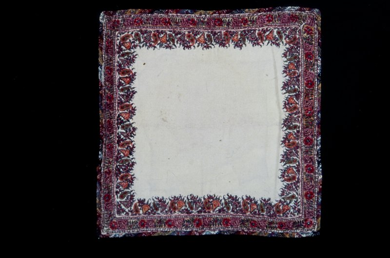 Square mat of white woolen material with border embroidered in silk and cotton threads in design of small palmettes, leaves and flowers. Wool.
