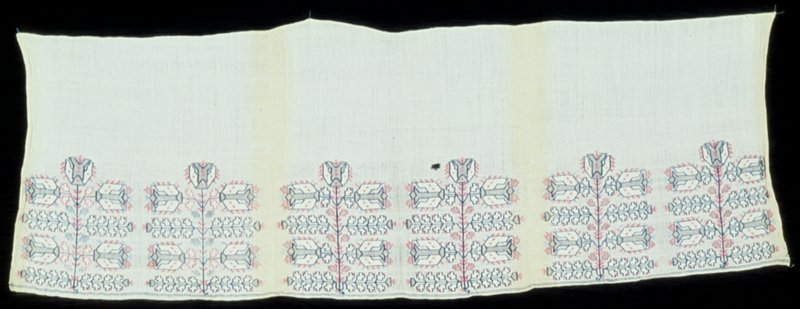 Three border ends of towel scarves sewn together. The linen materal is embroidered with meetal and linen thread in conventionalized flowerg plant motifs. Each of the three sections has cream silk borders woven into the sides of the material. White, pink, and blue threads are used.