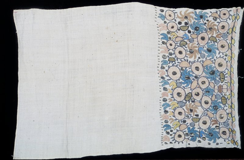 towel, end, linen, heavily embroidered with stylized roses, pinks(?), and lilies and leaves in shades of blue, green, yellow floss and tinsel thread; border of stem stitch flanked by leaves, across bottom