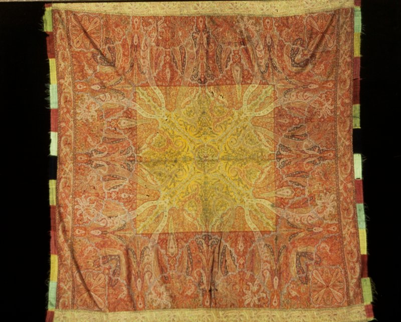 kussaba, or square shawl, having a center of yellow wool woven with leafy sprays. The border, woven separately and added, is on a red ground covered with floral butha and fantastic leaf designs; there is a second narrower border and a final border of strips of fringed woolen