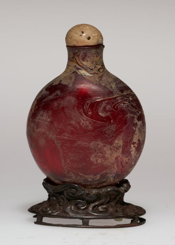 bottle, old mortuary red glass with stopper and stand; the glass has become iridescent through burial, and although used as a snuff bottle, was probably originally used for eye medicines