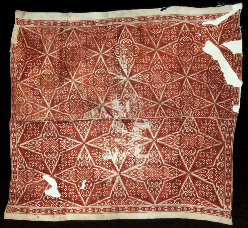 Cover, of brown linen, embroidered all over in quatrefoil lozenge design with henna silk in surface darning stitch. A seam runs from end to end through the center.