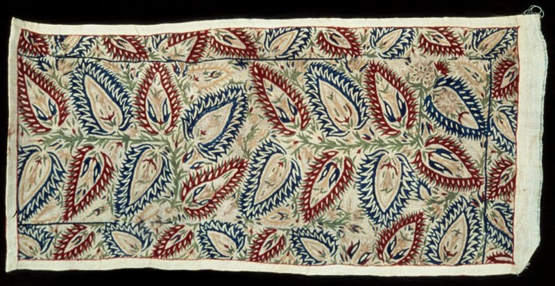 Linen strip, with a design of geometrical flowers and leaves embroidered in blue, red, green, and yellow silks in herringbone stitch. One complete and two partial borders remain. They contain a smaller version of the flower motif. The strip is lined with red satin.