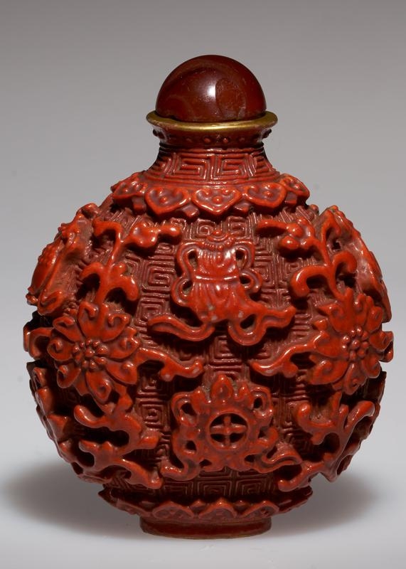 Snuff bottle; red porcelain in imitation of cinnabar lacquer. Symbolic ornament in relief covers entire body against ground of 'wall of China' motif.