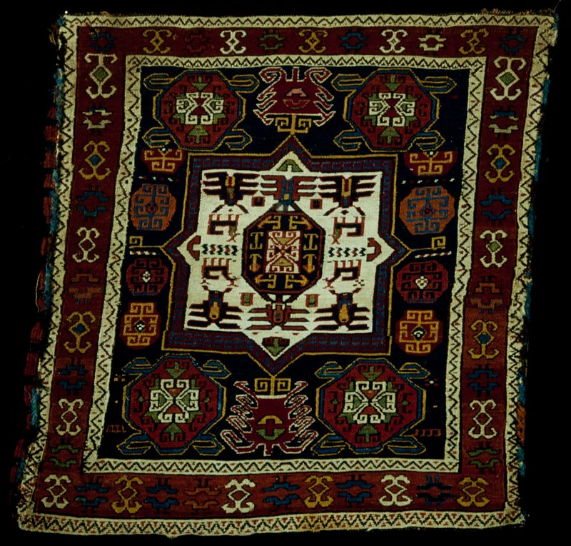 Pillow Case, Shemaka or Soumak, with typical geometric designs in tan, red, blue, green and yellow. A wide border with geometrical designs on a red ground is flanked by narrow borders carrying the reciprocal sawtooth in black on a beige ground, sides overcast with colored yarns, blocked with green cotton fabric. Woolen warp and woof.