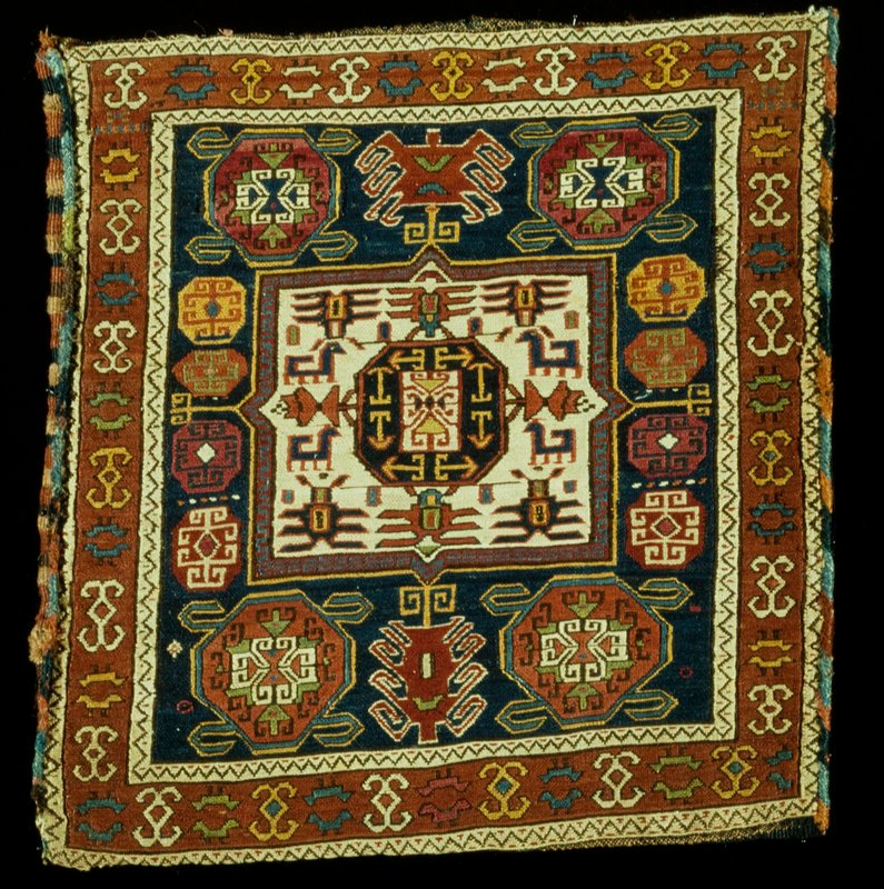 Shemaka or Soumak Pillow Case with typical geometric designs in tan, red, blue, green and yellow. A wide border with geometrical designs on a red ground, is flankled by narrow borders carrying the reciprocal sawtooth in black on a beige ground. Sides overcast with colored yarns, backed with green cotton fabric.