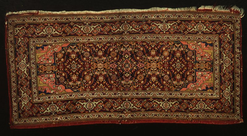 Rugs, with floral designs in dark blue, red, green, and yellow. The corners of the field have a stiff floral design on a field of old rose, central medallion has an all-over pattern. Three borders, one being the tortoise design. This piece is woven like a Soumak but has the designs of a Persian Kurdistan. Sides overcast. Woolen warp and weft.