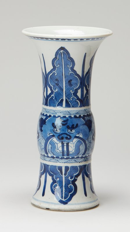 vase of beaker form with flaring mouth; white ground; design in brilliant underglaze blue of conventionalized palm border which springs, neck and base, from slightly bulbous belt, the latter ornamented with dragon heads and the 'wicker diaper' border
