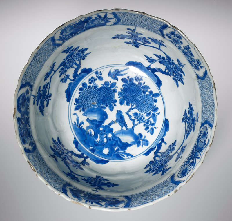 bowl, large, blue on white porcelain, decorated with petal-shaped panels containing flowers and birds; a medallion in the bottom of the bowl shows bird and flowers. This is surrounded by four hawthorne trees, and the inner rim is decorated with five floral medallions with intervening diaper design.