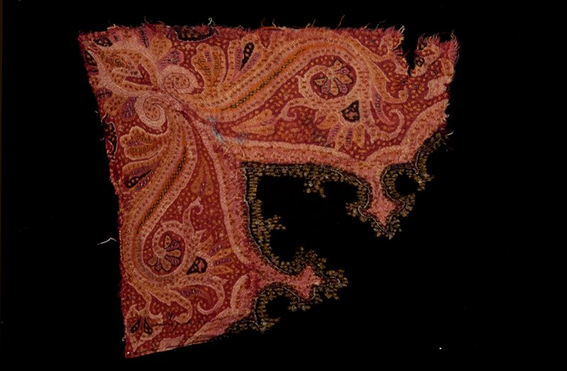 corner fragment of an Indian shawl; border in shades of rose with black center, conventional scroll and floral design