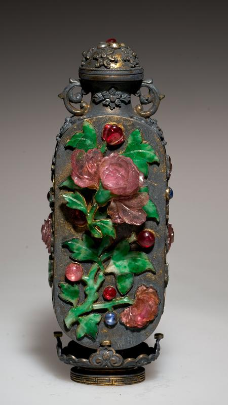 Snuff bottle (one of pair 36.5.2-3), gold inlaid on two flat sides with a large floral spray of semi-precious stones. Smaller floral designs in semi-precious stones on narrow sides. Two handles formed of gold scrolls. Gilt stand.