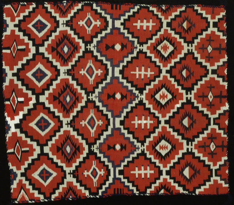 rug, finely woven, with a design of interlocking stepped lozenge medallions outlined in black and white on red ground; the medallions contain different motifs basaed on the lozenge or cruciform form; sides overcast in black yarn; tassels at corners